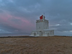 Beautiful view of historic white colored lighthouse (built 1927) on Dyrhólaey peninsula on the southern coast of Iceland in the evening with purple colored sky and brown grass in winter season.