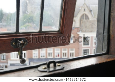 Beautiful View Of Historical Gouda Town Out Of The Old Window. Historic Highlights Of The Netherlands. Dark And Light Background.