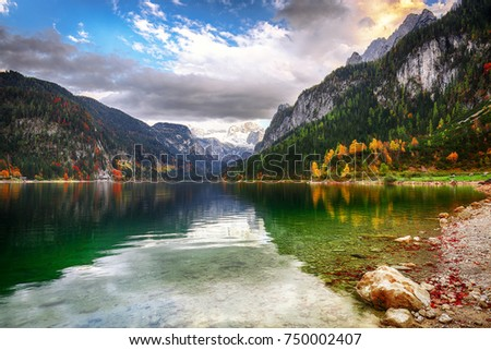 Beautiful view of idyllic colorful autumn scenery with Dachstein mountain summit reflecting in crystal clear Gosausee mountain lake in fall Salzkammergut region Upper Austria Austria - Shutterstock ID 750002407
