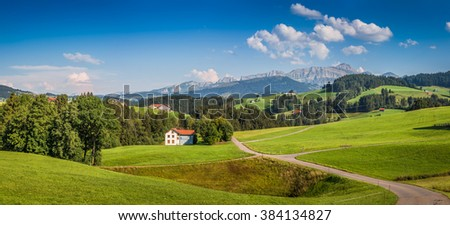 Beautiful view of idyllic mountain scenery in the Alps with green meadows and famous Saentis summit in the background on a sunny day with blue sky and clouds in summer, Appenzellerland, Switzerland