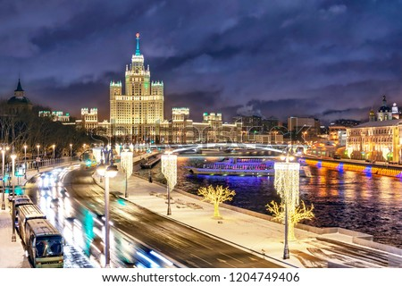 Beautiful view of illuminated Stalin skyscraper on the festive illumination Kotelnicheskaya embankment and Moscow River at night in Moscow, Russia.