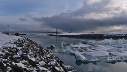 Beautiful view of Jökulsárlón suspension bridge, part of ring road (route 1) in southern Iceland with floating icebergs on the glacial lake on cloudy day in winter season.