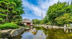 Beautiful view of Japanese Garden in Planten un Blomen park with famous Heinrich-Hertz-Turm radio telecommunication tower in the background, Hamburg, Germany