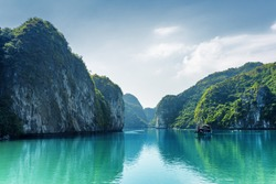 Beautiful view of lagoon in the Halong Bay (Descending Dragon Bay) at the Gulf of Tonkin of the South China Sea, Vietnam. Landscape formed by karst towers-isles on blue sky background.