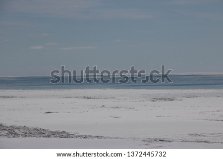 Beautiful view of Lake Erie Ontario Canada; From the top of an eroding cliff along the shore; Land being reclaimed by water; Snow and frozen water with open water in the distance; Beautiful blue sky   #1372445732