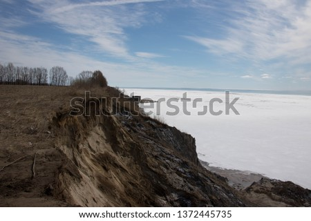 Beautiful view of Lake Erie Ontario Canada; From the top of an eroding cliff along the shore; Land being reclaimed by water; Snow and frozen water with open water in the distance; Beautiful blue sky   #1372445735
