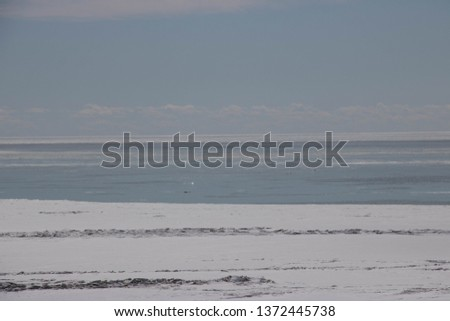 Beautiful view of Lake Erie Ontario Canada; From the top of an eroding cliff along the shore; Land being reclaimed by water; Snow and frozen water with open water in the distance; Beautiful blue sky   #1372445738
