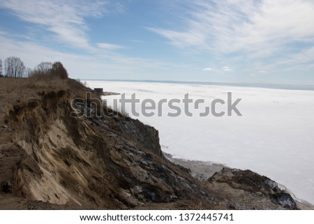 Beautiful view of Lake Erie Ontario Canada; From the top of an eroding cliff along the shore; Land being reclaimed by water; Snow and frozen water with open water in the distance; Beautiful blue sky   #1372445741