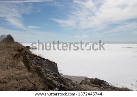 Beautiful view of Lake Erie Ontario Canada; From the top of an eroding cliff along the shore; Land being reclaimed by water; Snow and frozen water with open water in the distance; Beautiful blue sky   #1372445744