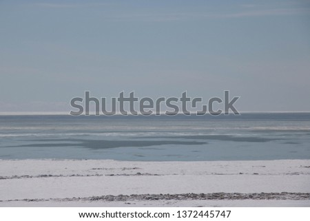 Beautiful view of Lake Erie Ontario Canada; From the top of an eroding cliff along the shore; Land being reclaimed by water; Snow and frozen water with open water in the distance; Beautiful blue sky   #1372445747