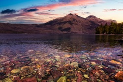 Beautiful View of Lake McDonald with American Rocky Mountains in the background. Cololful Sunrise Sky Art Render. Taken in Glacier National Park, Montana, United States of America.