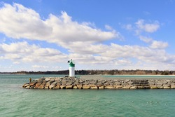 Beautiful view of Lake Ontario with a person by the lighthouse along the breakwater pier in Pickering, Ontario, Canada