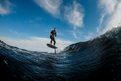 Beautiful view of man skillfully riding on the wave with hydrofoil foilboard on background of blue sky
