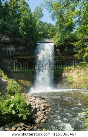 Beautiful view of Minnehaha Falls waterfall in Minneapolis Minnesota during day time in summer. Branch of mississippi river into flowing stream. Vertical framed stock photo.