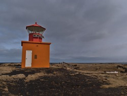 Beautiful view of orange colored Öndverðarnesviti lighthouse on the northwestern coast of Snæfellsnes peninsula, west Iceland in winter season with volcanic rocks and brown grass on cloudy day.