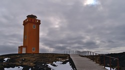Beautiful view of orange colored Svörtuloft lighthouse on the rough northwestern coast of Snæfellsnes, west Iceland in winter season with snow and wooden footpath on cloudy day.