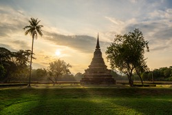 Beautiful view of pagoda with palm tree at Wat Mahathat inside the Sukhothai Historical Park, Thailand.