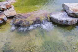 Beautiful view of pond decorated with big rocks. Clear water mirror surface effect.