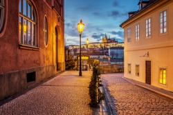Beautiful view of Prague Castle at sunset from a historical street with gas lamps over the river Vltava.