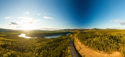 Beautiful View of Scenic Curvy Road from Above surrounded by Winding River, Forest and Mountains at Sunset. Aerial Drone Shot. Taken near Klondike Highway, Yukon, Canada.