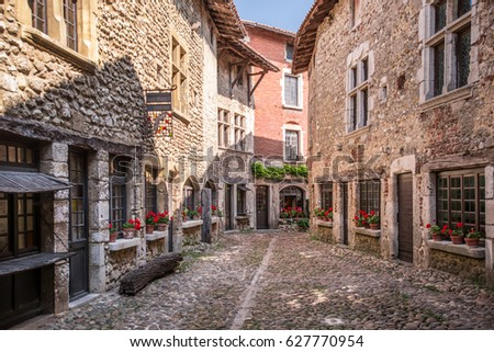 Beautiful view of scenic narrow alley with historic stone houses and cobbled street in an old town Perouge in France.