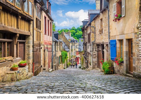 Beautiful view of scenic narrow alley with historic traditional houses and cobbled street in an old town in Europe with blue sky and clouds in summer with retro vintage Instagram grunge filter effect #400627618
