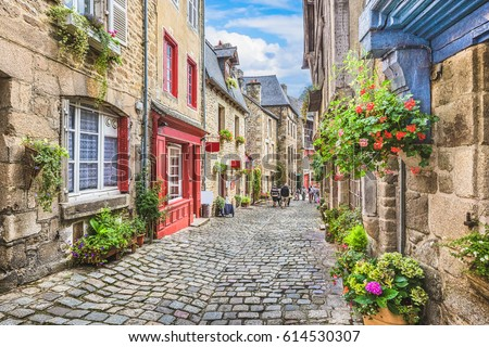 Beautiful view of scenic narrow alley with historic traditional houses and cobbled street in an old town in Europe with blue sky and clouds in summer with retro vintage Instagram grunge filter effect #614530307