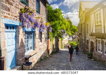 Beautiful view of scenic narrow alley with historic traditional houses and cobbled street in an old town of Dinan with blue sky and clouds. Brittany (Bretagne), France #685571047