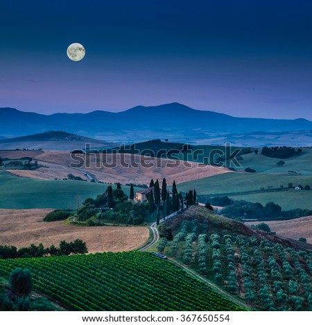 Beautiful view of scenic Tuscany landscape with rolling hills and valleys in beautiful moonlight at dawn, Val d'Orcia, Italy