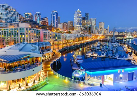 Beautiful view of Seattle waterfront and skyline at blue hour. Marina at pier 66, the great wheel (ferris wheel) can be seen in distance at far left corner. Travel and urban architecture background.