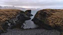 Beautiful view of small rocky beach on rough Atlantic coast of Snæfellsnes, west Iceland near Arnarstapi in winter with flying fulmar birds, rugged volcanic basalt rocks and snow-covered mountains.