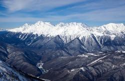 Beautiful view of snow covered mountain range and valley in Krasnaya Polyana. Caucasian mountains. Sochi, Krasnodar Krai