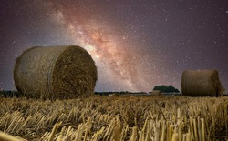 Beautiful view of starry night sky with milky way over harvested hay field with hay bales in the Kempen area, Belgium
