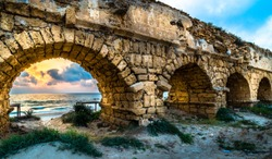 Beautiful view of sunset on the beach through the Caesarea aqueduct - ancient aqueduct built by Herod the Great along the Mediterranean shore; Israel