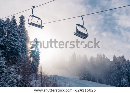 Beautiful view of the cabelway throw the snow forest in the mountain in the sunset