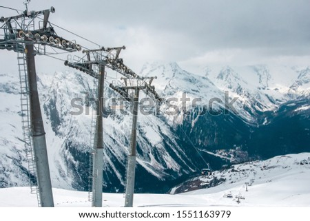 Beautiful view of the cableway in the snowy mountains. Metal poles in the form of poles. Transportation of tourists in a winter ski resort.