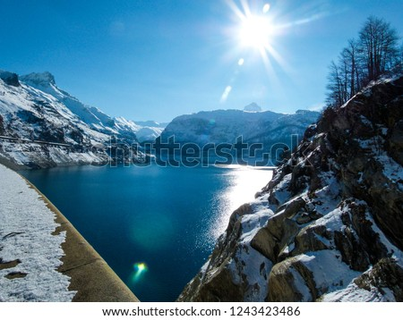 Beautiful view of the dam and alpine mountain lake, bright blue sky and sun in winter in Tignes, France