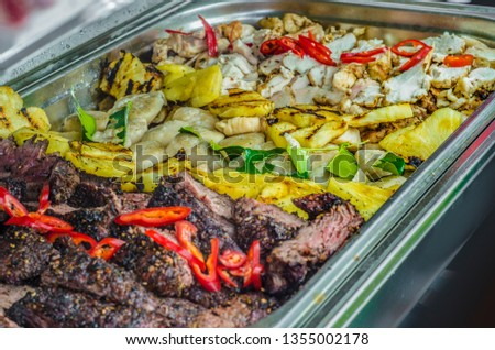Beautiful view of the food. A beautiful background and view of assorted portions of sliced finely delicious, wholesome vegetables, greens, peppers and pineapples with pieces of fried meat.