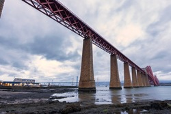 Beautiful view of the Forth Bridge, the Unesco heritage site in Edinburgh, Scotland. View under the suspended brick bridge at North Queensferry crossing the Nordic sea at sunset