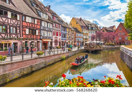 Beautiful view of the historic town of Colmar, also known as Little Venice, with tourists taking a boat ride along traditional colorful houses on idyllic river Lauch in summer, Colmar, Alsace, France