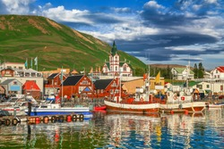 Beautiful view of the historic town of Husavik with traditional colorful houses and traditional fisherman boats lying in the harbor in golden evening light at sunset, northern coast of Iceland