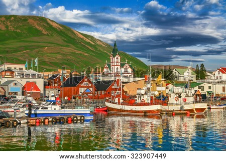 Beautiful view of the historic town of Husavik with traditional colorful houses and traditional fisherman boats lying in the harbor in golden evening light at sunset, northern coast of Iceland #323907449
