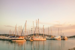 Beautiful view of the marina: yachts with masts against the background of the islands in the light of the setting sun