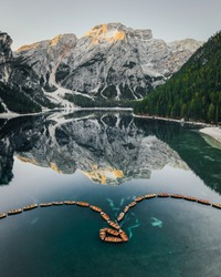 Beautiful view of the mountain lago di Braies in the Dolomites. Mirror reflection of a mountain in a lake. Morning mountain summer landscape of boats on the water.