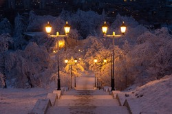 Beautiful view of the night winter city park. A ladder in the snow goes down. Lanterns by the road illuminate the path. Background for a greeting card. High quality photo