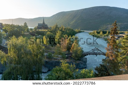 Beautiful view of the part Lom village during summer sunset. Medieval wooden Stave Church stavkyrkje from twelve century and Trebro bridge. Stock fotó ©