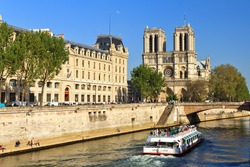Beautiful view of the river Seine with a canal-boat and the Notre-Dame Cathedral in Paris