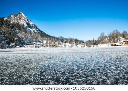 Beautiful view of  Timber  Boathouses or sheds or hotel at Konigssee and frozen Lake Konigssee with idyllic mountain scenery in winter near Berchtesgaden in German alp mountains.  Bavaria, Germany.