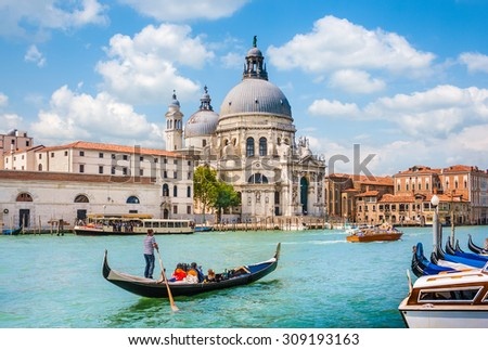 Beautiful view of traditional Gondola on Canal Grande with Basilica di Santa Maria della Salute in the background on a sunny day in Venice, Italy #309193163