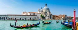 Beautiful view of traditional Gondolas on Canal Grande with historic Basilica di Santa Maria della Salute in the background on a sunny day in Venice, Italy